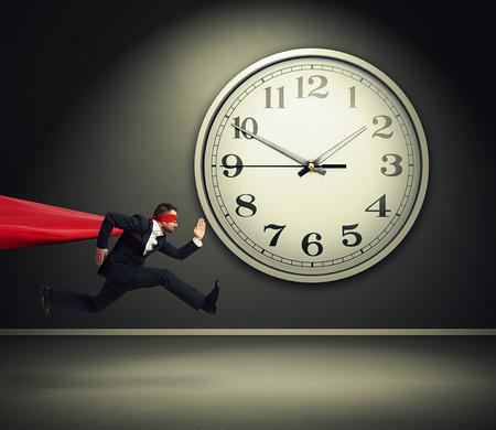 ernstige zakenman draagt als superman lopen tegen grote witte klok in een donkere kamer Stockfoto