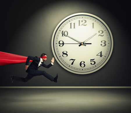 serious businessman wearing like superman running against big white clock in dark room Stock Photo