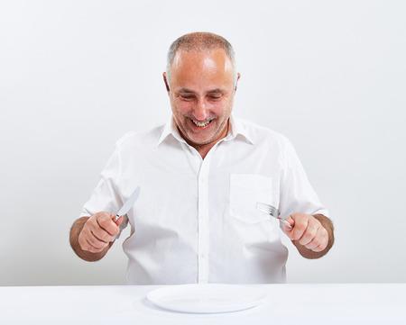 smiley Senior Mann hält Gabel mit Messer und Blick auf leere weiße Platte auf dem Tisch über hellgrauem Hintergrund