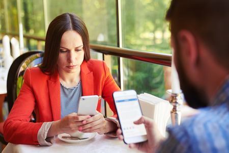 concept photo of smartphone addiction. young woman and man sitting in cafe with smartphone and do not looking at each other Foto de archivo