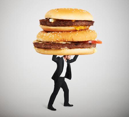 comida chatarra: pequeño hombre en ropa formal llevando grandes sándwiches de arriba contra el fondo gris claro Foto de archivo