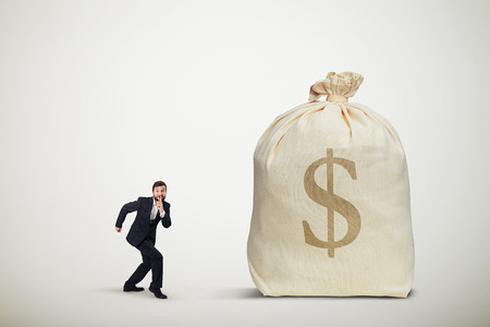 slink: businessman in formal wear showing silent sign and sneaking to the big bag of money over light grey background