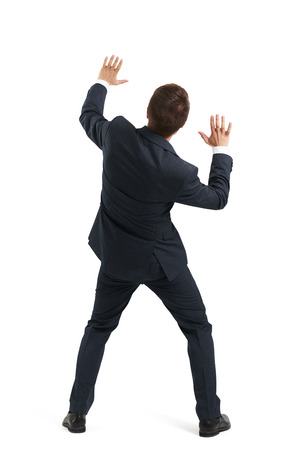 startled: back view of startled businessman in formal wear moving aside and covering hands. isolated on white background