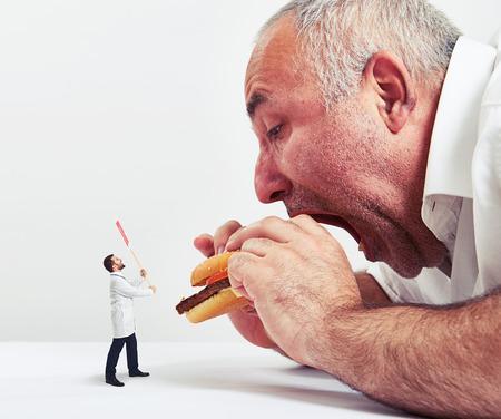 comida chatarra: cerca foto de hombre comiendo hamburguesa y pequeño doctor mirarlo y protestando contra la comida chatarra