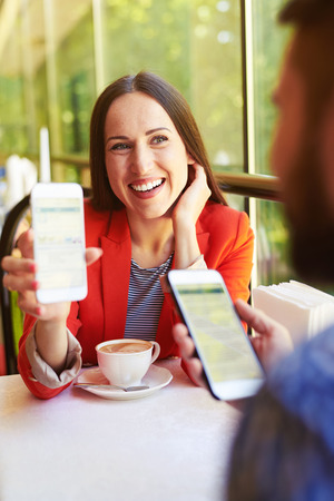 mobilephone: laughing young woman showing her mobilephone to man at cafe Stock Photo