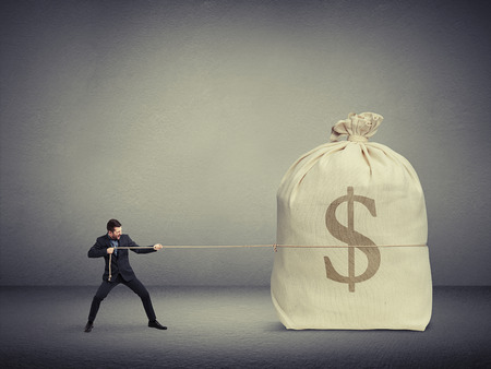 pulling money: small businessman pulling the rope a big bag of money over dark background