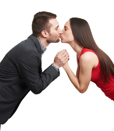 beso labios: retrato de la joven pareja cogidos de la mano y besando sobre fondo blanco