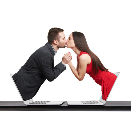 flirtation: young man got out of the computer and kissing beautiful young woman who got out of another computer over white background Stock Photo