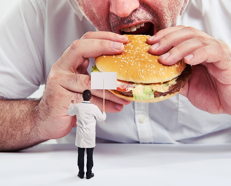 remonstrance: close up photo of man eating burger with french fries and small doctor looking at him and protesting against junk food Stock Photo