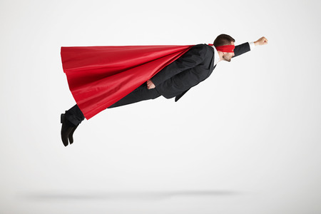 businessman dressed as a superhero in red mask and cloak flying up over light grey background