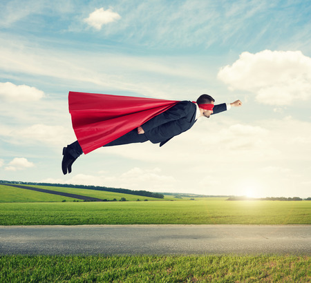 flying man: serious businessman dressed as a superhero in red mask and cloak flying at outdoor over beautiful landscape background Stock Photo