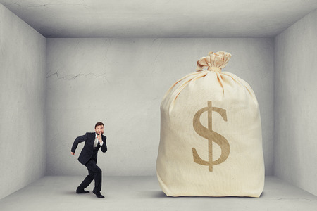 businessman in formal wear showing silent sign and walking on tiptoe to the big bag of money in grey room Stock Photo
