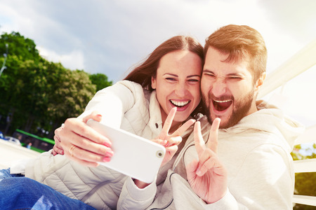 outdoors photo of joyous couple showing peace sign and taking selfie by mobilephone Stock Photo