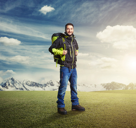 knapsack: happy tourist with knapsack smiling and looking at camera over beautiful landscape Stock Photo