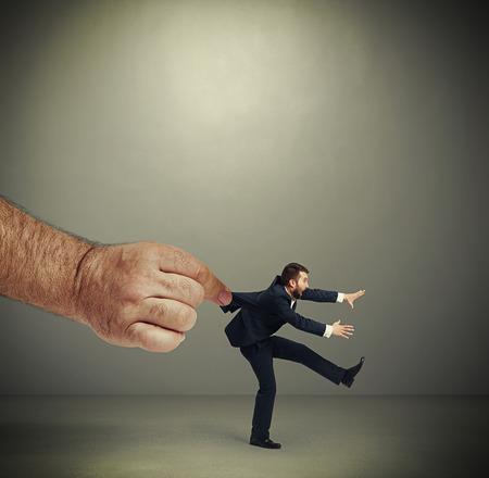 covet: big mans hand kepping emotional running businessman over dark grey background