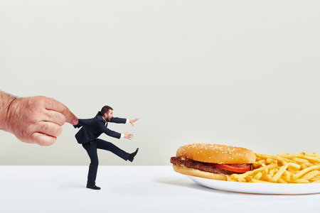 junks: small man running to junk food but the big hand holding him over light grey background