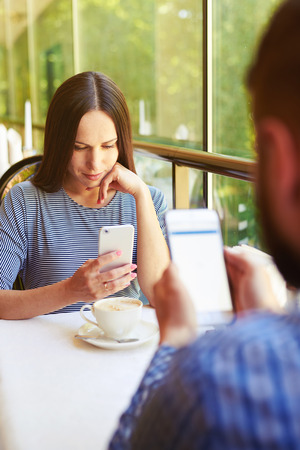 woman and man sitting on cafe and using their smartphones photo