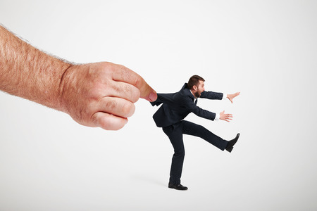fervour: big hand stopping running man in formal wear over light grey background Stock Photo