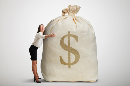 big: happy woman embracing big bag with money and smiling over light grey background