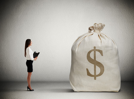 stocktaking: woman with folder standing in dark room and looking at big money bag Stock Photo