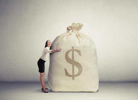 riches adult: happy woman embracing big bag with money and smiling in empty grey room