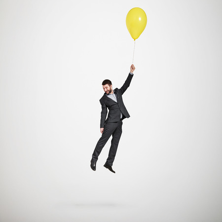 laughing man flying with yellow balloon and looking down over light grey background Stockfoto
