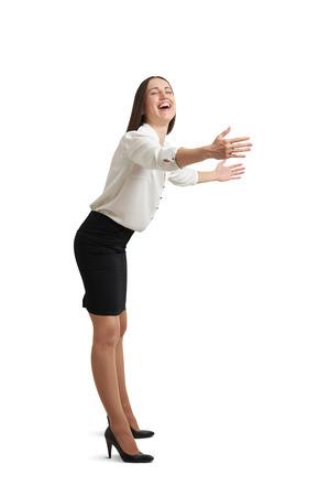 personas abrazadas: mujer feliz en ropa formal con los ojos cerrados riendo y estirando sus manos como listo para abrazo. aislado en fondo blanco Foto de archivo