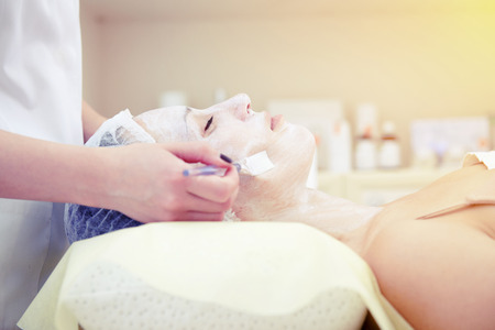 resting mask: doctor applying cosmetologists mask on womans face Stock Photo