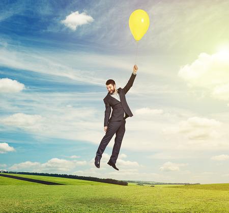 flying man: bright uotdoors photo of flying man with yellow balloon
