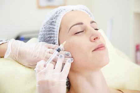 inyeccion: hermosa mujer que consigue una inyección en su cara en el salón de belleza