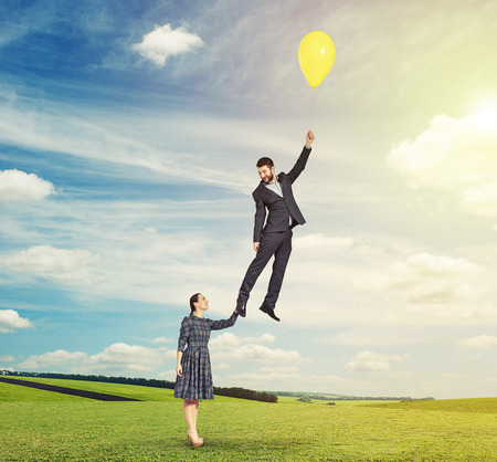 flying man: young beautiful woman holding flying man and looking at him. smiley man holding yellow balloon and looking at woman. photo at outdoor