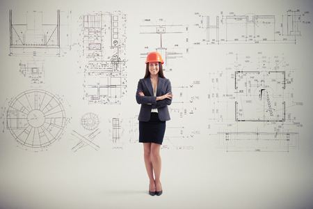 successfull: successfull woman in hardhat over grey wall with prints Stock Photo