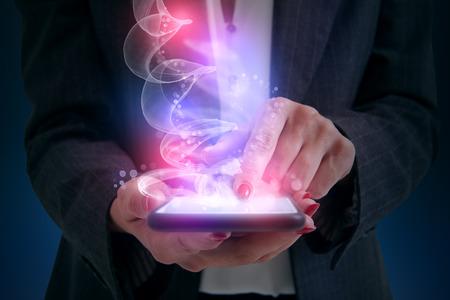 m�gica: Mujer tocando tel�fono inteligente y brillante m�gica viene de la pantalla Foto de archivo