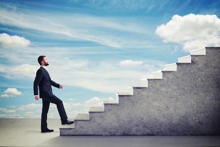 escalera: hombre de negocios sonriente en traje formal caminando por las escaleras en el cielo azul Foto de archivo