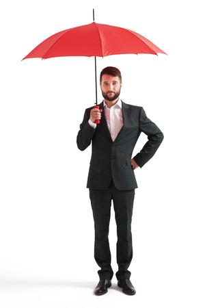 uomo rosso: imprenditore serio sotto l'ombrello rosso. isolato su sfondo bianco