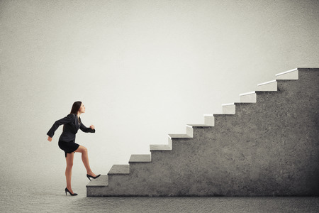 purposeful: purposeful woman in formal wear walking up stairs over light grey background