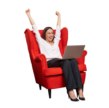 red chair: excited happy businesswoman with raised hands up sitting in red chair and looking at laptop Stock Photo