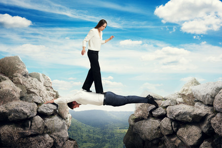 between: woman walking on the man which lying like bridge between two rocks