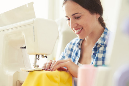 modiste: smiley young woman seamstress sewing yellow dress Stock Photo