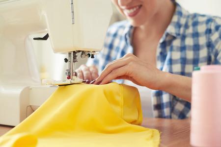 재봉 기계에 웃는 여자 바느질. 재봉 기계에 초점