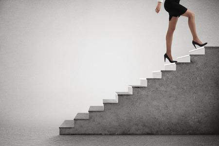 vrouw in formele slijtage traplopen over lichtgrijze achtergrond