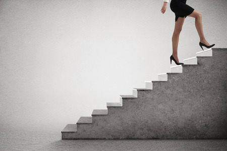business woman legs: woman in formal wear walking up stairs over light grey background Stock Photo