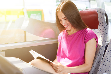 smiley woman reading book in the bus Banque d'images