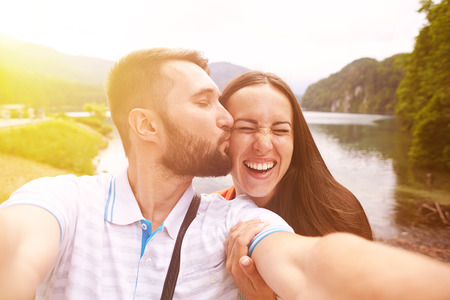 vacationers: happy couple taking selfie against beautiful view with lake and hills