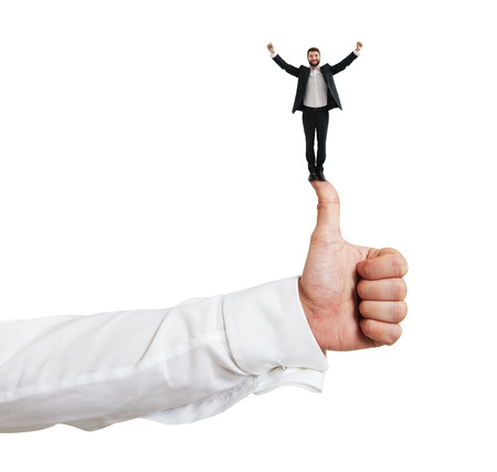 merriment: happy small businessman standing on big thumbs up and raising his hands up. isolated on white background