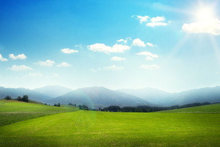 sky sun: beautiful sunny landscape of green meadow with hills Stock Photo