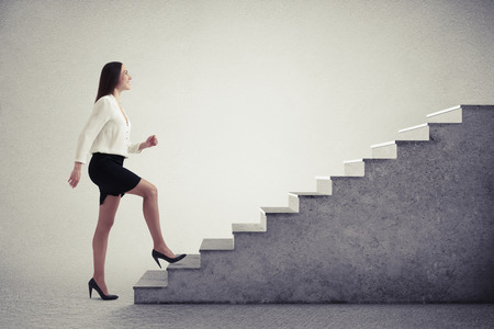 escaleras: empresaria sonriente en ropa formal subir escaleras sobre fondo gris claro Foto de archivo