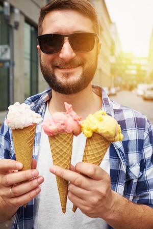 comiendo helado: soleado del hombre sonriente en gafas de sol con helado de tres