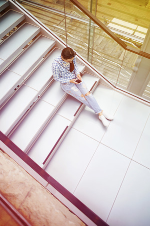 view woman: top view of young woman sitting on the stairs and using her smartphone