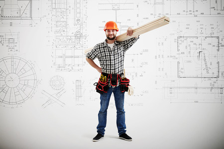 worker man: smiley builder in uniform holding long wooden boards over grey wall with prints Stock Photo